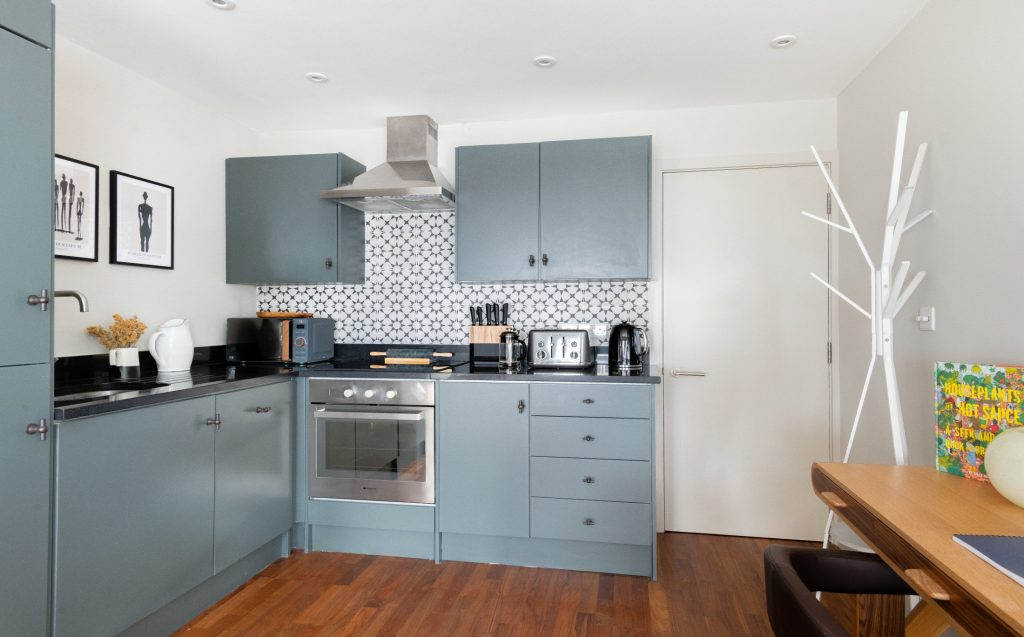The Kennington Escape, Bright and airy kitchen, coat stand, desk and modern kitchen with blue kitchen units and patterned tiles
