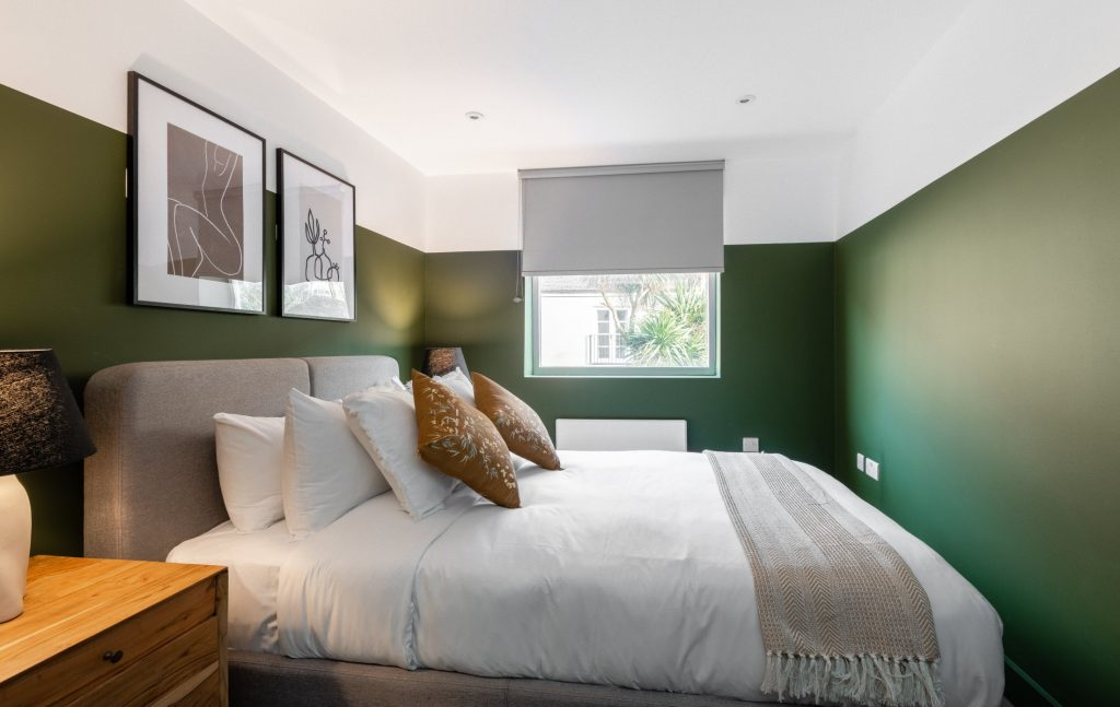 The Kennington Escape, large double bed, Olive Green walls, bedside table and lamp