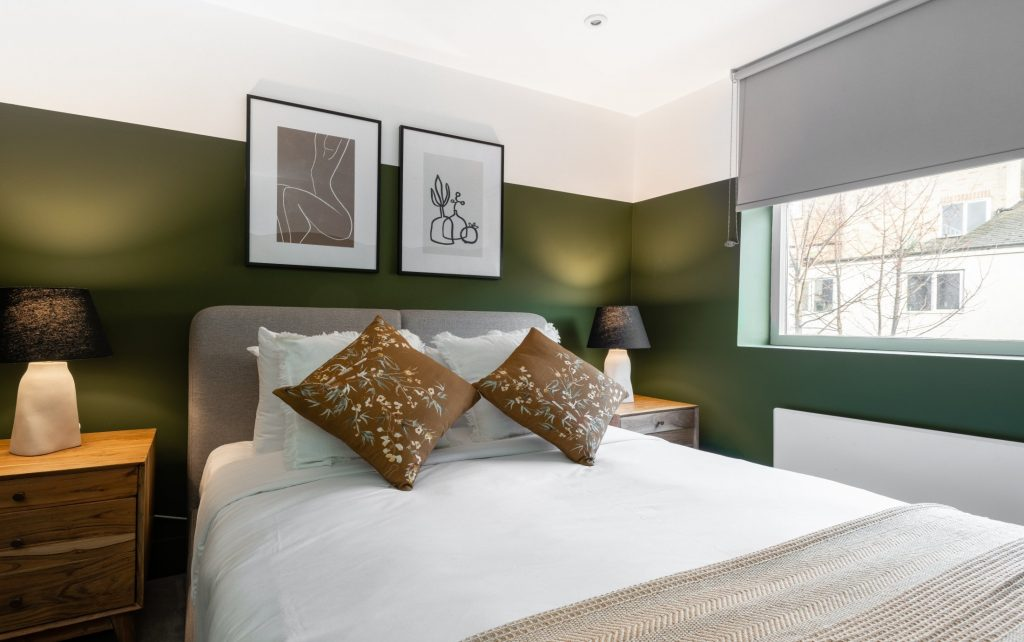 The Kennington Escape, double bed, floral scatter cushions, bedside table and lamp
