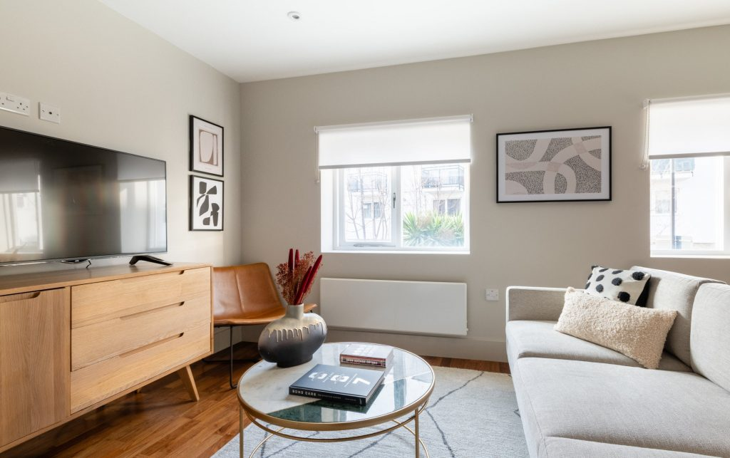 The Kennington Escape, Grey Sofa, large flat screen TV, Glass coffee table, cosy rug and wooden floor