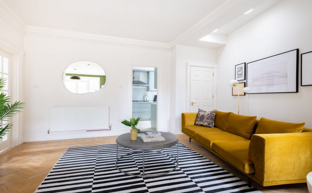 The Pimlico Townhouse, Living area, mustard sofa, walk through to kitchen, gallery wall pictures, mirror and house plants
