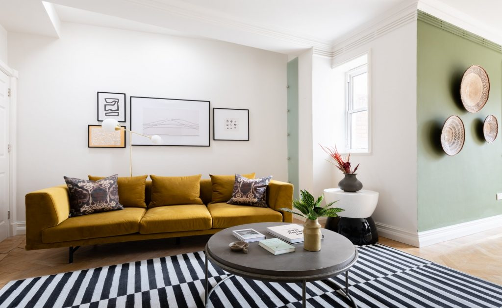 The Pimlico Townhouse, living area, Mustard Yellow sofa, black and white rug, coffee table and house plants