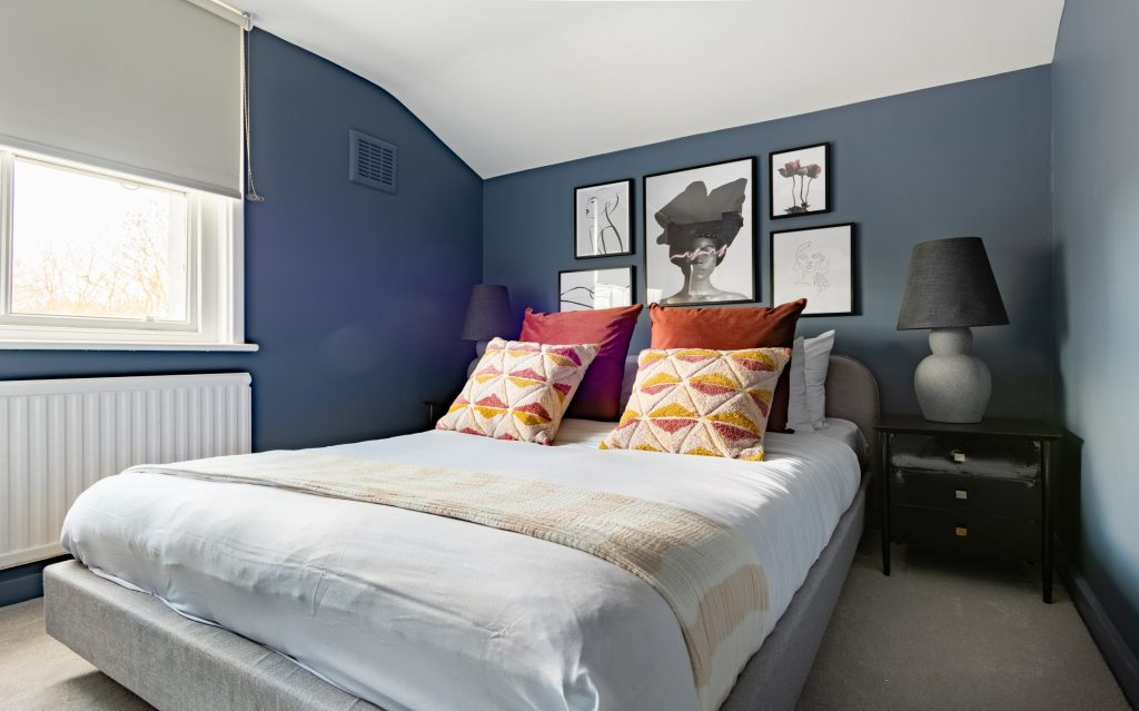 Blue walls, double bed and scatter cushions