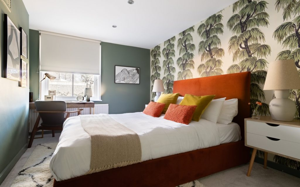 Large double bedroom, tropical wallpaper, orange bed with throw and scatter cushions