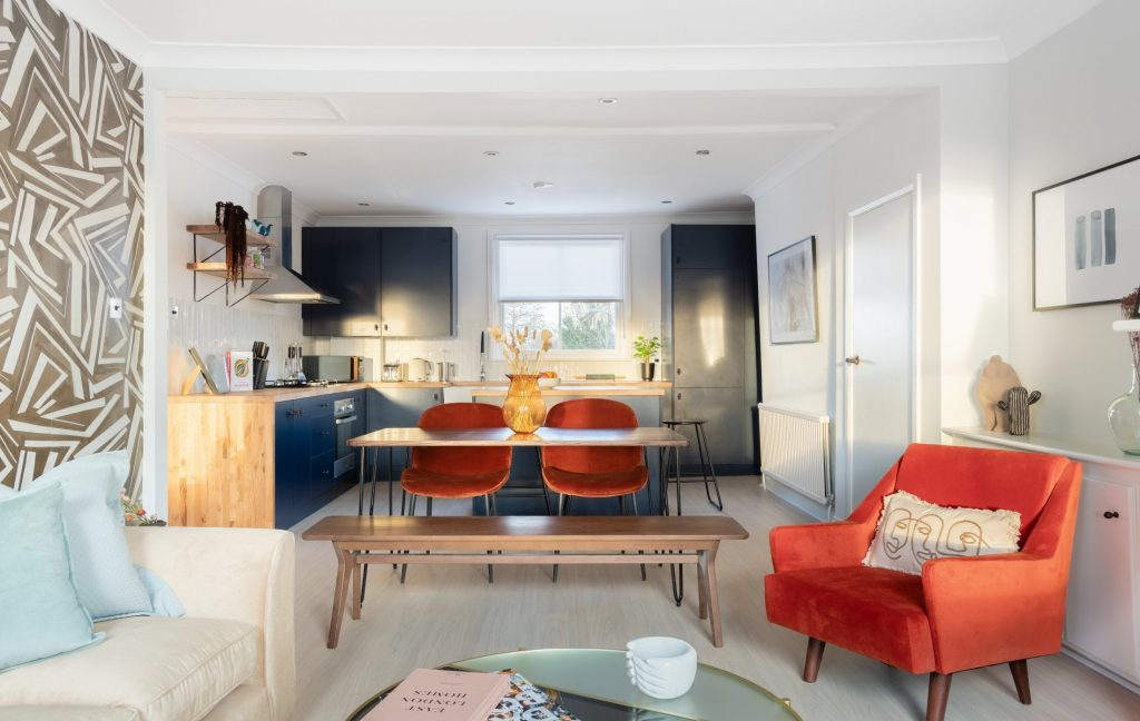 Kitchen, dining table and living area, sofa, armchair, navy blue kitchen units