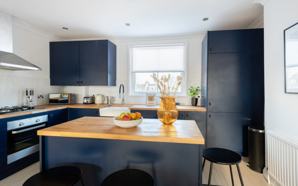 Blue modern kitchen, fruit bowl and house plants