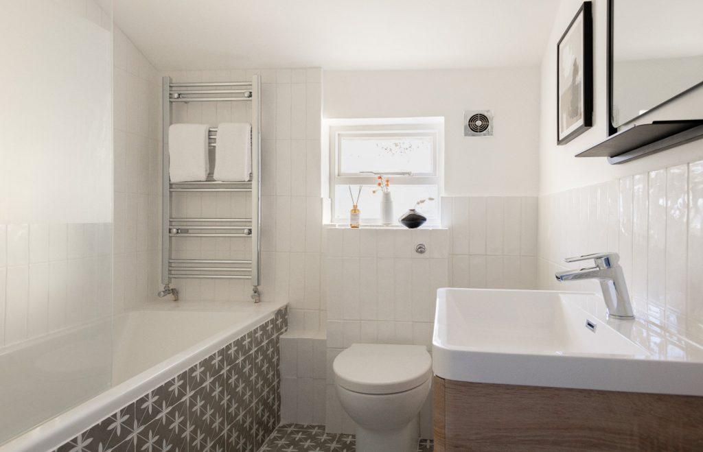 Bathtub, white bathroom, patterned tiles, toilet and sink