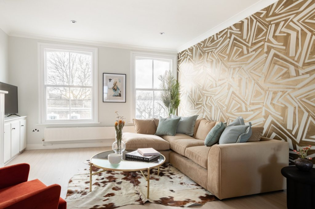 L shaped sofa, quirky wallpaper, armchair and rug
